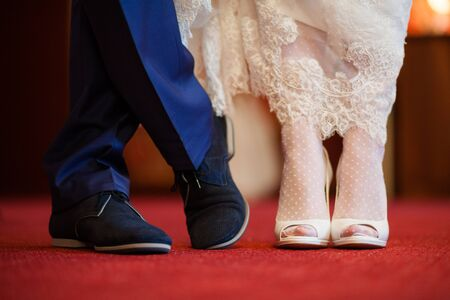 The legs of the groom in blue shoes and trousers. The bride in white heels with a snow-white hem of a wedding dress on the red floor