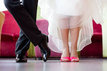 Legs of the groom in black shoes and trousers and brides in crimson heels with a snow-white hem of a wedding dress Reklamní fotografie
