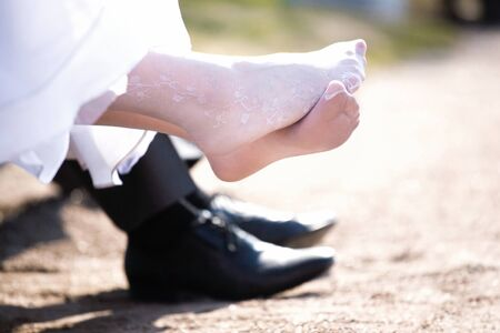 Groom legs in black shoes and pants and brides in white stockings with a snow-white hem of a wedding dress Reklamní fotografie