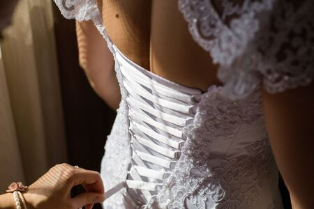 Bride from the back. Lacing the wedding dress.