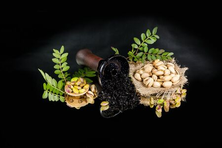 Hookah bowl with tobacco. Pistachio shisha tobacco. On a black background. Stock Photo