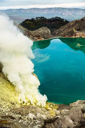 Crater of a volcano with a green sulfuric volcanic lake and volcanic smoke. View of the smoking volcano Kawah Ijen in Indonesia. Mountain landscape