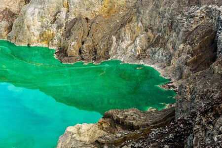 Shot of the shore of a green sulfur lake in the crater of the Kawah Ijen volcano in Indonesia