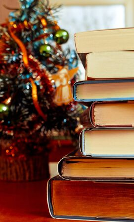 Books laying in front of Chrismas tree photo