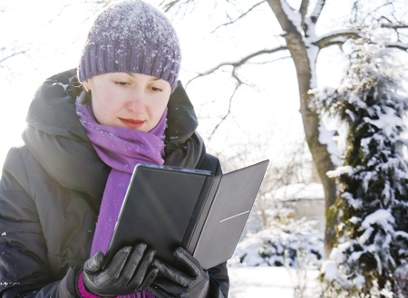 Young lady reading e-book outdoors at winter time
