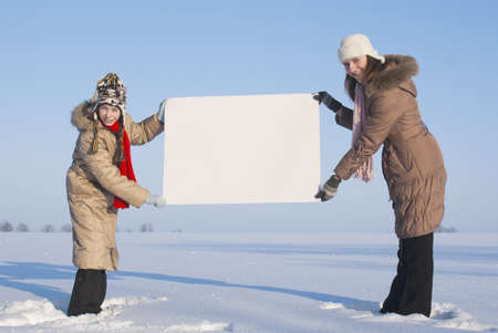 Girls holding white poster at winter snowy field Stock Photo - 8746359