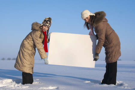 Girls holding white poster at winter snowy field Stock Photo - 8746364