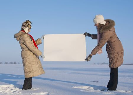 Girls holding white poster at winter snowy field Stock Photo - 8746365