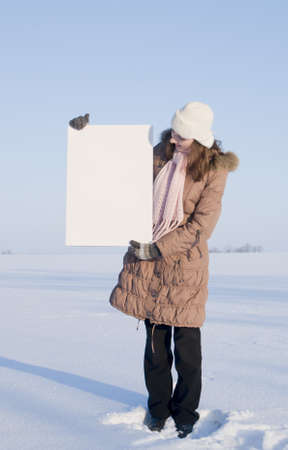 Girl holding white poster at winter snowy field Stock Photo - 8746362