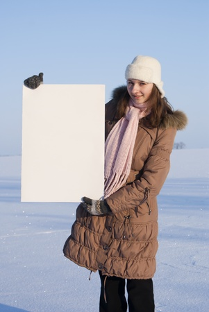 Girl holding white poster at winter snowy field Stock Photo - 8746367