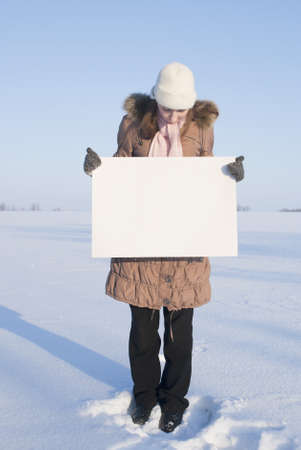Girl holding white poster at winter snowy field Stock Photo - 8746363