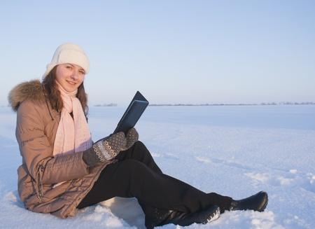 Teen girl reading e-book outdoors at winter time Stock Photo - 8746448