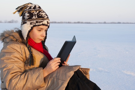 Teen girl reading e-book outdoors at winter time Stock Photo - 8746450