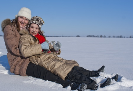 Two happy sisters sledding at winter time photo