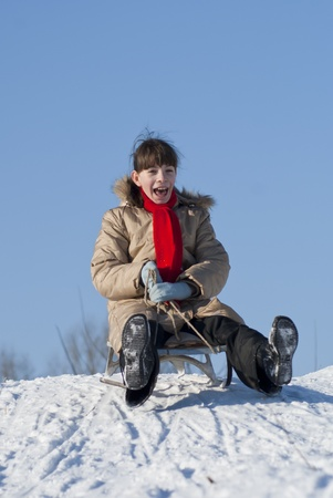 Teen girl sledding from a hill photo