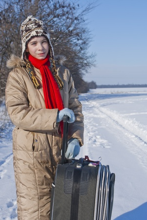 Teen girl with a suitcase outdoors at winter time photo