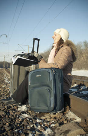 Teen girl sitting at the railroad and reading photo