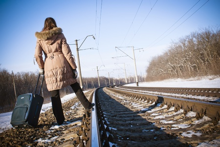 single track: Teen girl with a suitcase near the railways at winter time Stock Photo