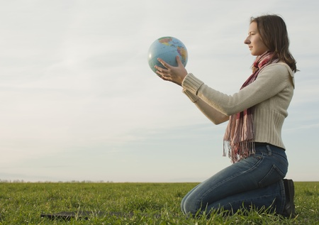 Teen girl sitting with a globe on the grass photo