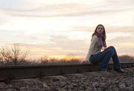 Teen girl sitting near the railways