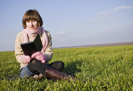 Young lady reading a book sitting at grass photo