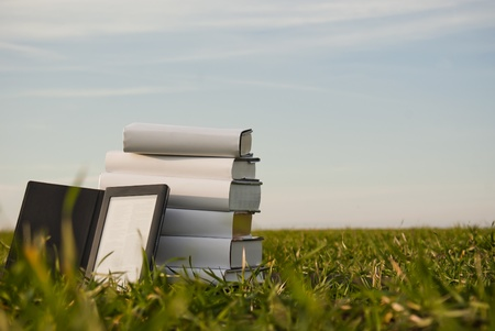 Stack of books with ebook reader outdoors laying on grass Stock Photo - 8926316
