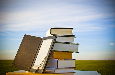 Stack of books with ebook reader outdoors laying on table Stock Photo - 8926318