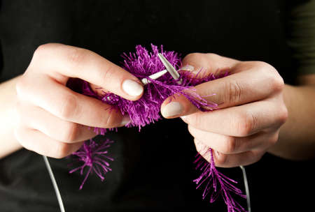 Hands knitting a thing with spokes isolated on black