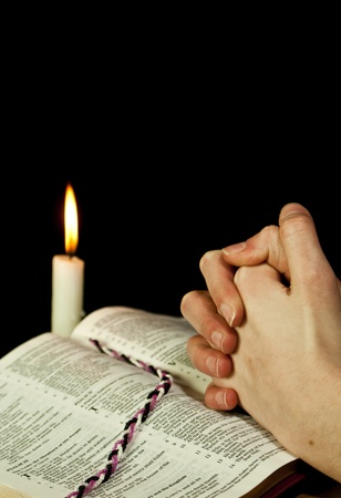 candle: Open Bible with burning candle and hands of praying woman Stock Photo
