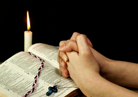 Open Bible with burning candle and hands of praying woman photo