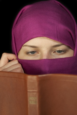 religious clothing: Teen girl muffled in a shawl readingg the Bible