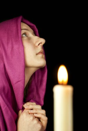 Eastern style dressed teen girl praying with a candle photo