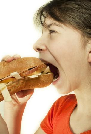 overeat: Teen girl eats a huge hamburger Stock Photo