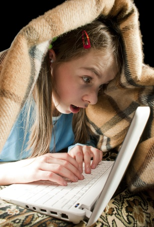 Teen girl with laptop serfing and hiding under blanket photo