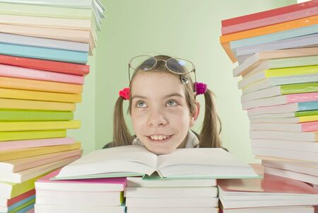 homestudy: School girl sitting at the table with stacks of books Stock Photo