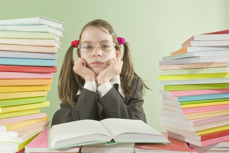 Bored school girl sitting at the table with stacks of books photo