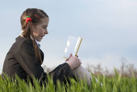 Girl with a book sitting on the grass Stock fotó