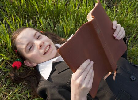 Girl with the Bible laying on the grass photo