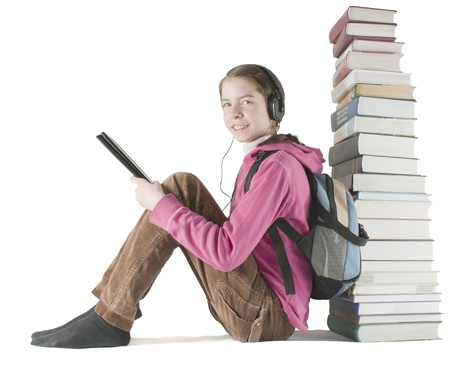Teen girl reads ebook sitting near the stack of printed books photo