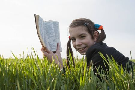 field study: Teen girl with the Bible laying on grass Stock Photo