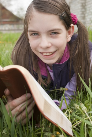 Teen girl reads book laying on grass photo