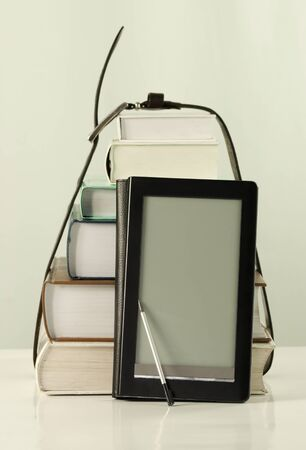 Stack of books and electronic book reader on the white background