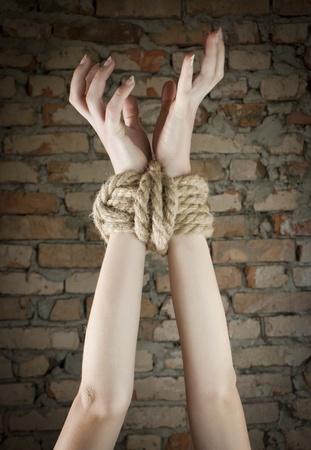 Hände mit Seilen gefesselt