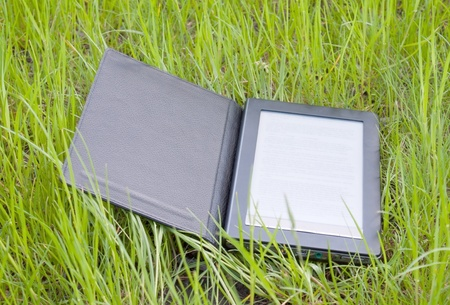 Electronic book reader laying on grass