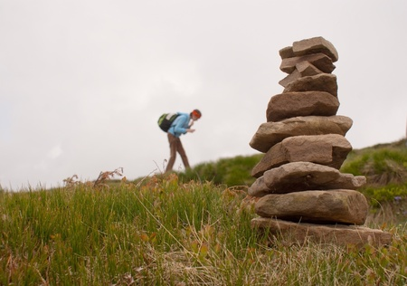 heap: Stack of stones with teen girl tourist on background