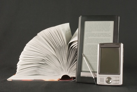 Open book, electronic book reader and hand held computer on black background Stock Photo - 9805931