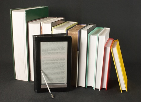 Row of printed books with electronic book reader on black background Stock Photo - 9805932