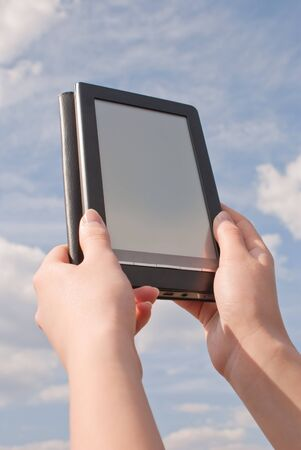 Hands hold electronic book reader against blue sky Stock Photo - 9805930