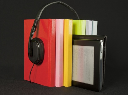 electronic background: Audiobooks concept -  Colorful books with headphones and electronic book reader on black background