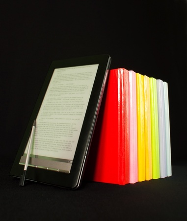 Row of colorful books and electronic book reader on the black background Stock Photo - 9925670
